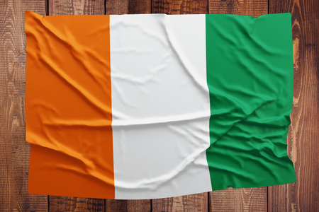 Flag of Cote DIvoire on a wooden table background. Wrinkled Ivorian flag top view.