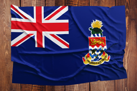 Flag of Cayman Islands on a wooden table background. Wrinkled flag top view.