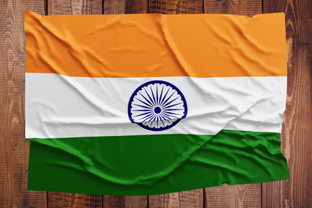 Flag of India on a wooden table background. Wrinkled Indian flag top view.