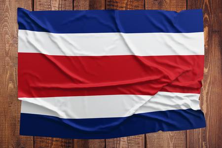 Bandera de Costa Rica sobre un fondo de mesa de madera. Vista superior de la bandera de Costa Rica arrugada.