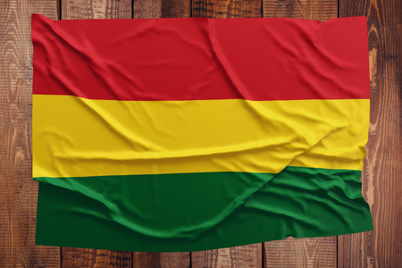 Flag of Bolivia on a wooden table background. Wrinkled Bolivian flag top view. Stock Photo