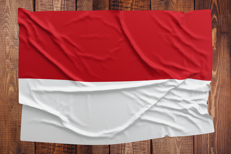 Flag of Indonesia on a wooden table background. Wrinkled Indonesian flag top view.