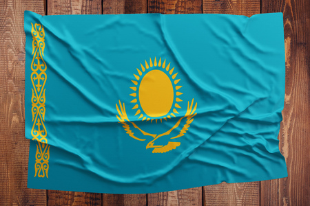 Flag of Kazakhstan on a wooden table background. Wrinkled Kazakh flag top view.