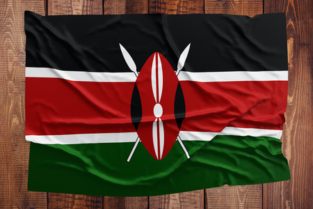Flag of Kenya on a wooden table background. Wrinkled Kenyan flag top view. Stock Photo