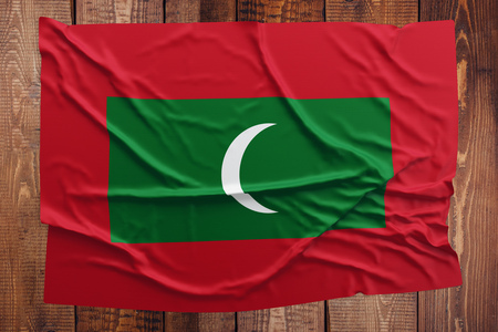 Flag of Maldives on a wooden table background. Wrinkled Maldivan flag top view.