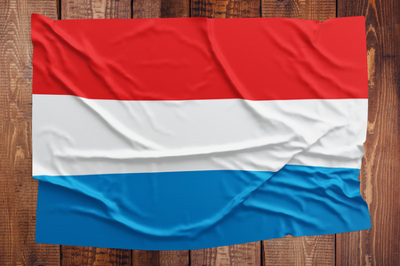 Flag of Luxembourg on a wooden table background. Wrinkled Luxembourger flag top view. Stock Photo