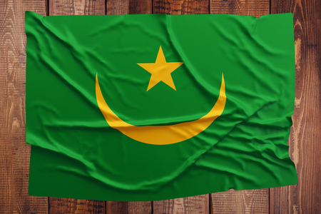 Flag of Mauritania on a wooden table background. Wrinkled Mauritanian flag top view.