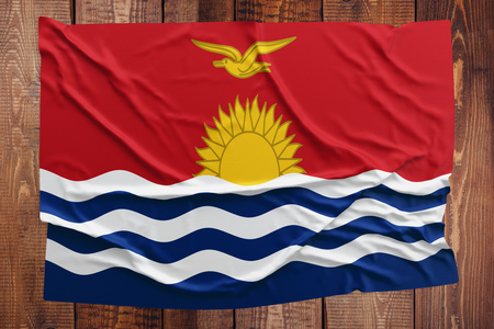 Flag of Kiribati on a wooden table background. Wrinkled flag top view. Stock Photo