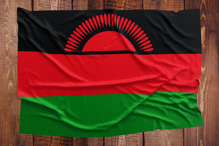 Flag of Malawi on a wooden table background. Wrinkled Malawian flag top view.