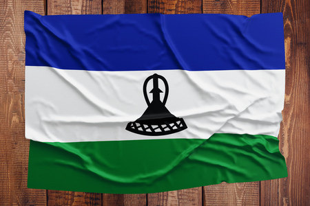Flag of Lesotho on a wooden table background. Wrinkled Mosotho flag top view. Stock Photo