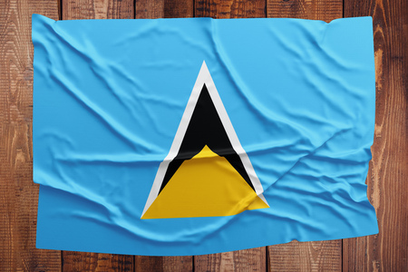 Flag of Saint Lucia on a wooden table background. Wrinkled flag top view. Stock Photo