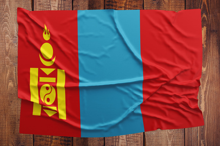 Flag of Mongolia on a wooden table background. Wrinkled Mongolian flag top view.