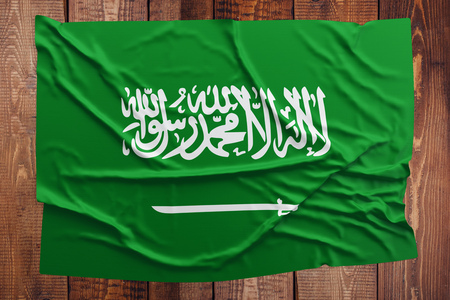 Flag of Saudi Arabia on a wooden table background. Wrinkled Saudi flag top view. Archivio Fotografico