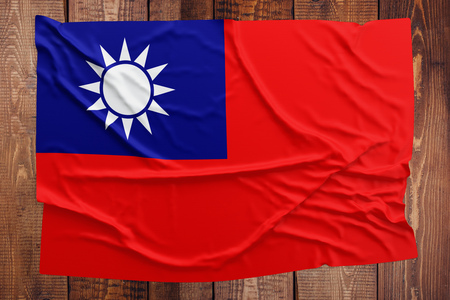 Flag of Taiwan on a wooden table background. Wrinkled Taiwanese flag top view. Stock Photo