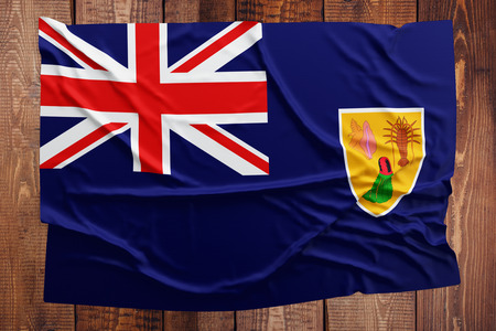 Flag of Turks And Caicos Islands on a wooden table background. Wrinkled flag top view.