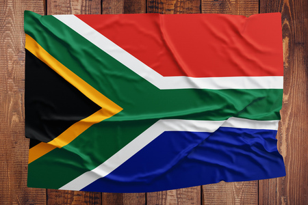 Flag of South Africa on a wooden table background. Wrinkled South African flag top view.