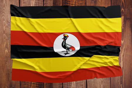 Flag of Uganda on a wooden table background. Wrinkled Ugandan flag top view.