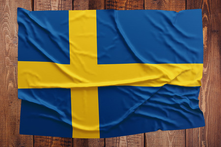 Flag of Sweden on a wooden table background. Wrinkled Swedish flag top view.