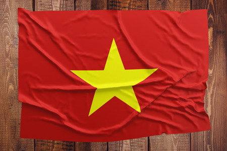 Flag of Vietnam on a wooden table background. Wrinkled Vietnamese flag top view. Stock Photo