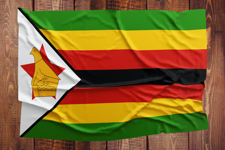 Flag of Zimbabwe on a wooden table background. Wrinkled Zimbabwean flag top view.