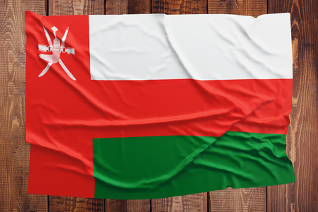 Flag of Oman on a wooden table background. Wrinkled Omani flag top view. Stock Photo