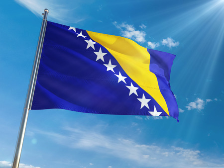 Bosnia Herzegovina National Flag Waving on pole against sunny blue sky background. High Definition Stock Photo