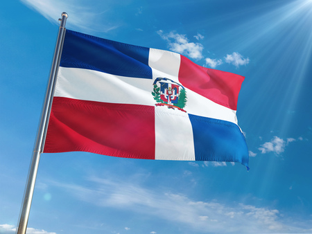 Dominican Republic National Flag Waving on pole against sunny blue sky background. High Definition
