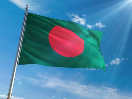 Ondear la bandera nacional de Bangladesh en la pole contra el fondo de cielo azul soleado. Alta definición