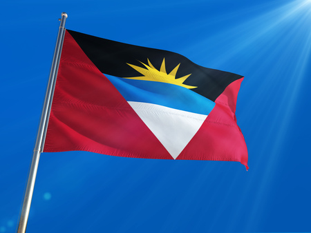 Antigua and Barbuda National Flag Waving on pole against deep blue sky background. High Definition