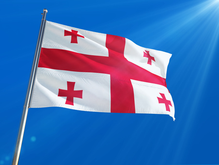 Georgia National Flag Waving on pole against deep blue sky background. High Definition Stock Photo