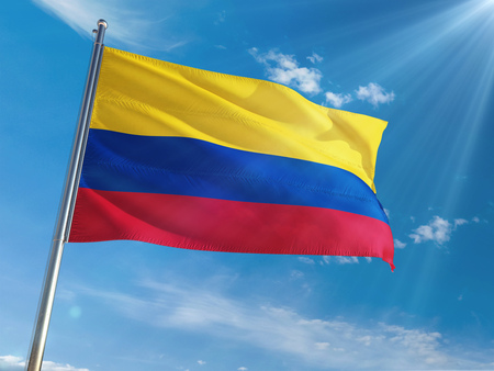 Colombia National Flag Waving on pole against sunny blue sky background. High Definition