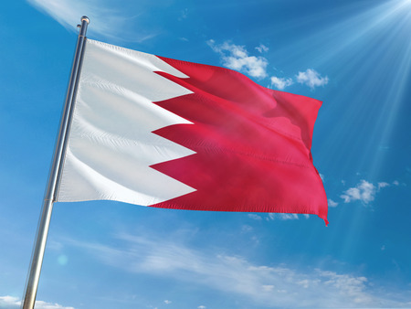 Bahrain National Flag Waving on pole against sunny blue sky background. High Definition Standard-Bild