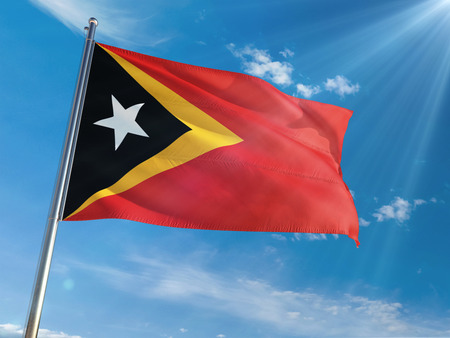East Timor National Flag Waving on pole against sunny blue sky background. High Definition