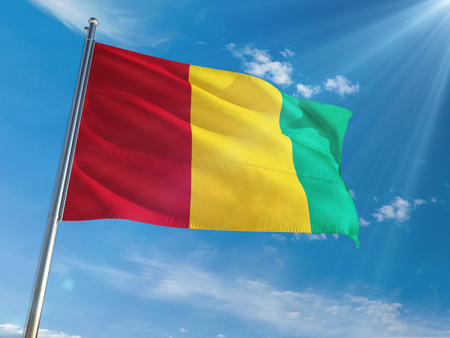 Guinea National Flag Waving on pole against sunny blue sky background. High Definition Stock Photo