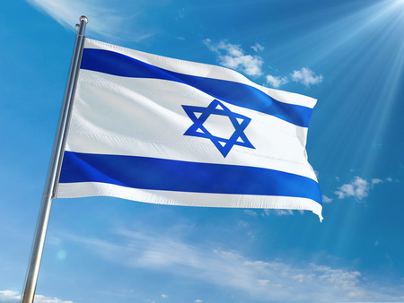 Israel National Flag Waving on pole against sunny blue sky background. High Definition Фото со стока