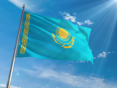 Kazakhstan National Flag Waving on pole against sunny blue sky background. High Definition 스톡 콘텐츠