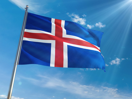 Iceland National Flag Waving on pole against sunny blue sky background. High Definition