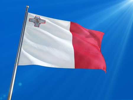 Malta National Flag Waving on pole against deep blue sky background. High Definition