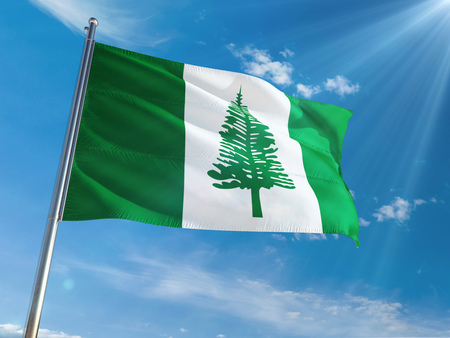 Norfolk Island National Flag Waving on pole against sunny blue sky background. High Definition