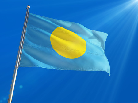Palau National Flag Waving on pole against deep blue sky background. High Definition