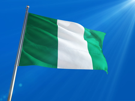 Nigeria National Flag Waving on pole against deep blue sky background. High Definition