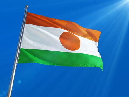 Niger National Flag Waving on pole against deep blue sky background. High Definition
