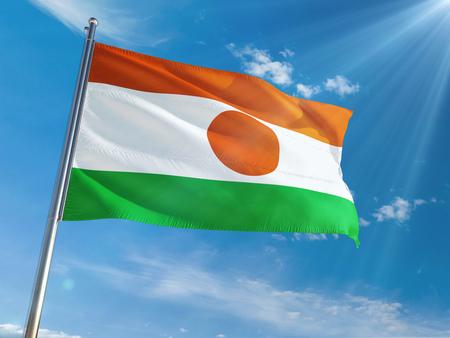 Niger National Flag Waving on pole against sunny blue sky background. High Definition