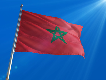 Morocco National Flag Waving on pole against deep blue sky background. High Definition