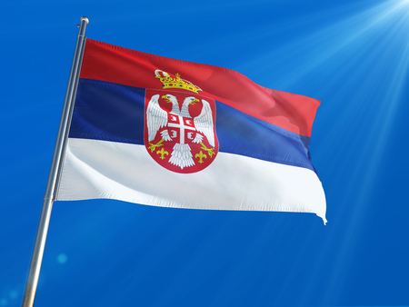 Serbia National Flag Waving on pole against deep blue sky background. High Definition Stock Photo