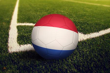 Netherlands ball on corner kick position, soccer field background. National football theme on green grass. Foto de archivo