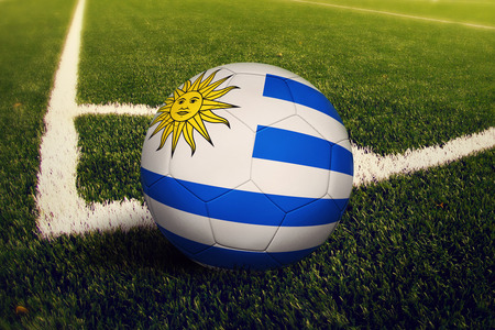 Uruguay ball on corner kick position, soccer field background. National football theme on green grass.