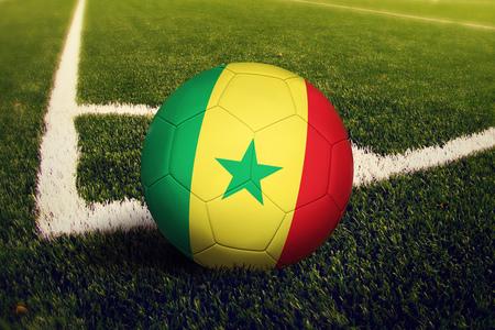 Senegal ball on corner kick position, soccer field background. National football theme on green grass.