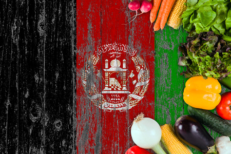 Fresh vegetables from Afghanistan on table. Cooking concept on wooden flag background.