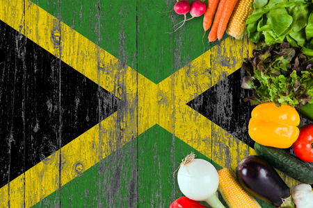 Fresh vegetables from Jamaica on table. Cooking concept on wooden flag background. Stock Photo - 117121118